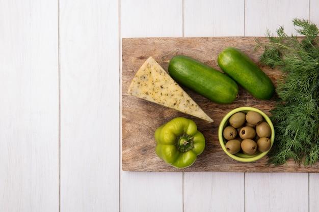 Vue de dessus copie espace fromage avec concombres et poivrons sur un support avec olives sur fond blanc