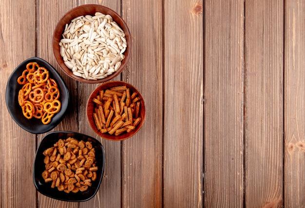 Vue de dessus copie espace graines blanches dans des bols avec des bagels et de la chapelure sur un fond en bois
