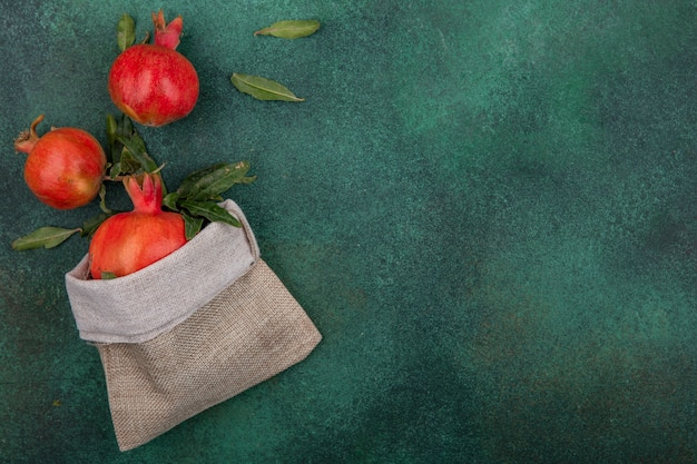 Vue de dessus copie espace grenades avec des feuilles dans un sac de jute sur fond vert
