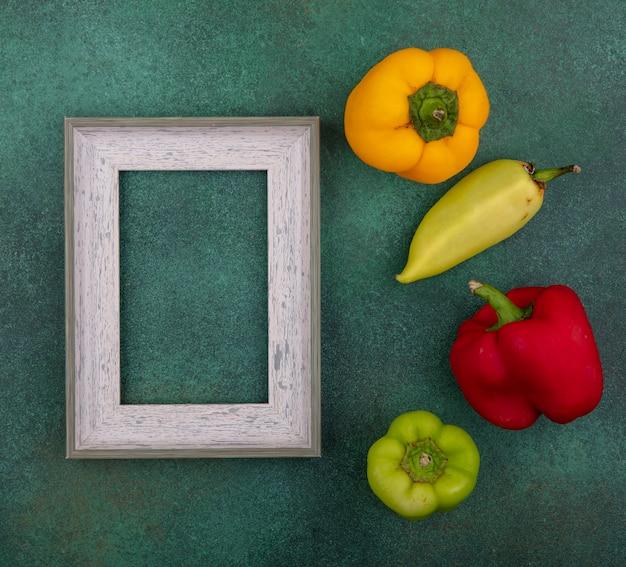 Vue de dessus copie espace gris avec des poivrons colorés sur fond vert