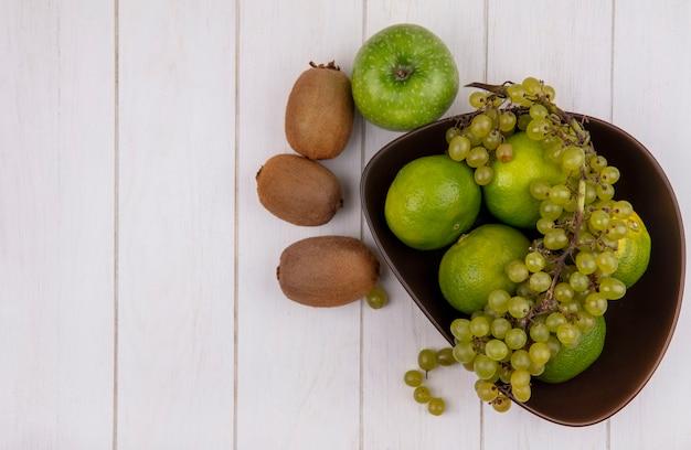 Vue de dessus copie espace kiwi avec pomme et raisins avec mandarines dans un bol sur mur blanc