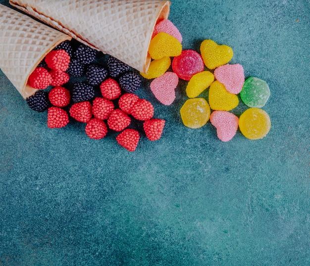Vue de dessus copie espace marmelade en forme de framboises, mûres et coeurs avec des cornets gaufres sur fond vert foncé