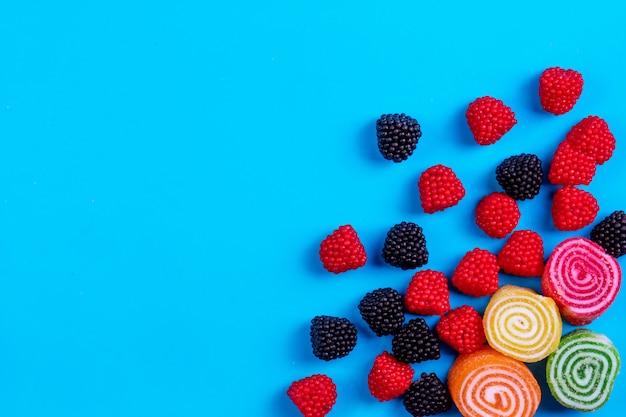 Vue de dessus copie espace marmelades multicolores avec des marmelades en forme de framboises et mûres sur fond bleu