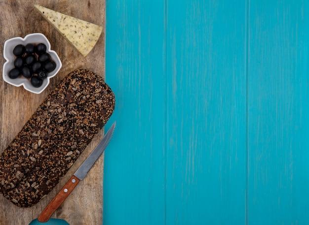 Vue de dessus copie espace pain noir sur un support avec des olives au fromage dans un bol sur un fond turquoise