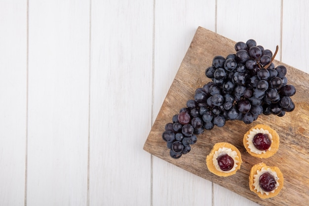 Vue de dessus copie espace tartelettes avec raisins noirs sur une planche à découper sur fond blanc