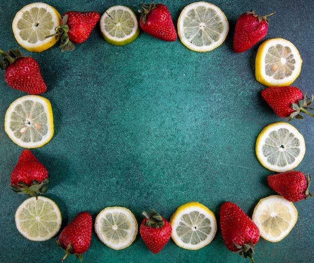 Vue de dessus copie espace tranches de citron et citron vert aux fraises sur vert