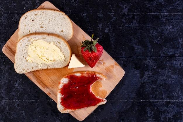 Vue de dessus copie espace tranches de pain et de beurre avec une tranche de pain avec de la confiture à bord avec des fraises