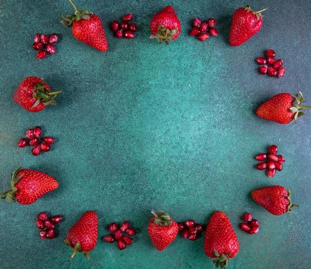 Vue de dessus copie des fraises de l'espace avec de la grenade pelée sur les bords sur le vert