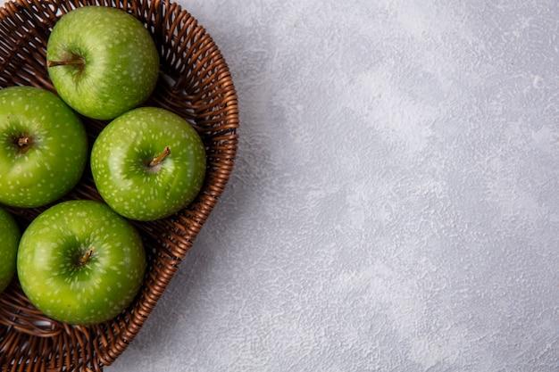 Vue de dessus copiez les pommes vertes de l'espace dans un panier sur fond blanc