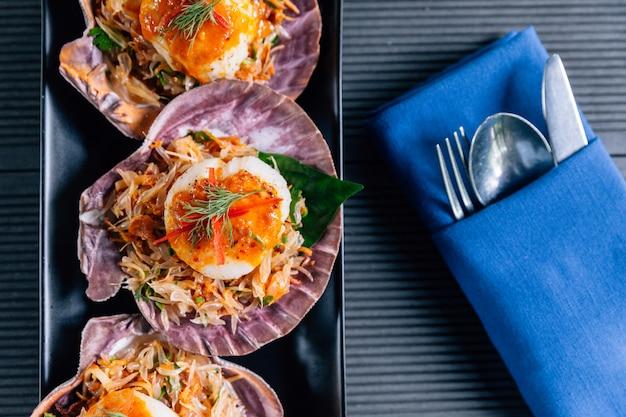 Vue de dessus de coquille saint-jacques en coquillage avec salade de pomelo épicée servie dans une assiette noire.