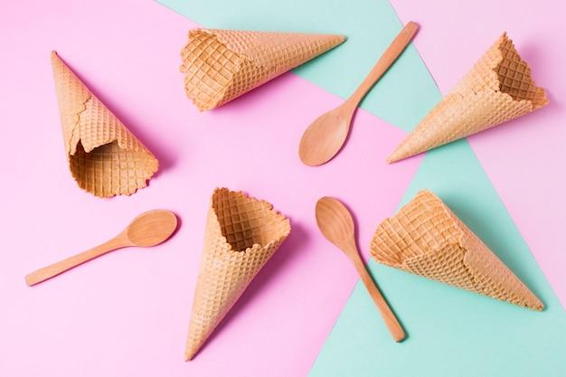 Vue de dessus des cornets de crème glacée et des cuillères en bois