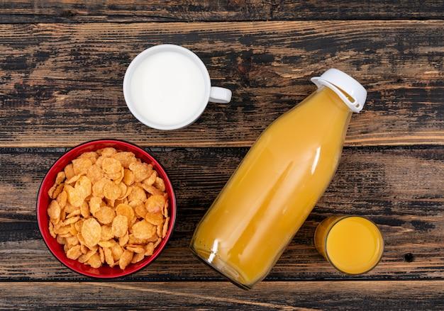 Vue de dessus des cornflakes avec du jus et du lait sur une surface en bois sombre horizontal