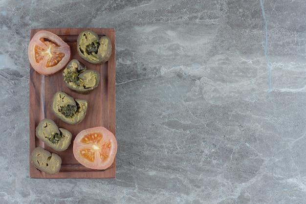 Vue de dessus cornichon tomate verte et rouge sur planche de bois.
