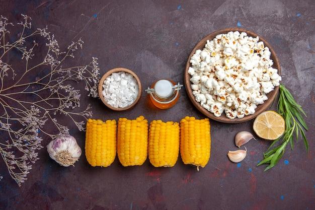 Vue de dessus des cors jaunes crus avec du maïs soufflé frais sur un bureau sombre des films de maïs soufflé planter du maïs