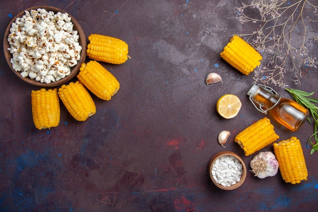 Vue de dessus des cors jaunes frais avec du pop-corn sur la surface sombre des collations de maïs crues fraîches
