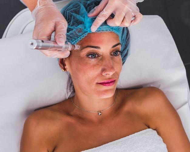 Vue de dessus d'un cosmétologue professionnel effectuant une procédure de mésothérapie avec des micro-aiguilles dermapen à une femme adulte dans un salon de beauté, une clinique de cosmétologie.