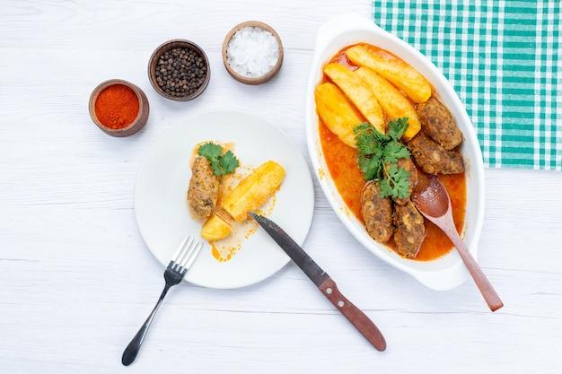 Vue de dessus des côtelettes de viande cuites avec pommes de terre en sauce et assaisonnements verts sur la lumière, repas alimentaire viande légume poivron