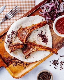 Vue de dessus de côtes d'agneau kebab aux oignons rouges sur une planche de bois