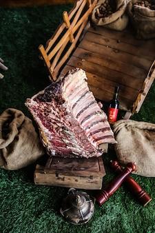 Vue de dessus des côtes de viande crue sur un plateau avec une bouteille de sacs de toile de jute de vin rouge sur l'herbe
