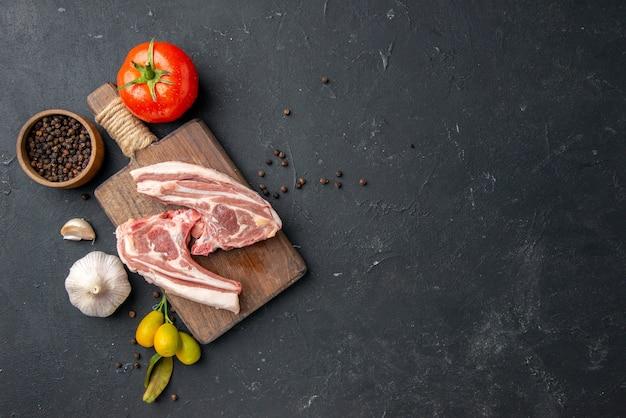Vue de dessus côtes de viande fraîche viande crue avec assaisonnements sur barbecue noir plat animal poivre cuisine nourriture vache salade repas repas