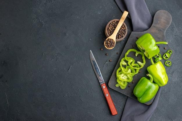 Vue de dessus de la coupe entière de poivrons verts hachés sur une planche à découper en bois sur une surface de couleur foncée