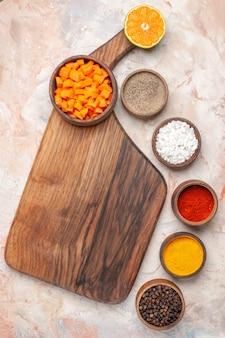 Vue de dessus couper la carotte dans un bol sur une planche à découper différentes épices dans de petits bols sur une surface nue