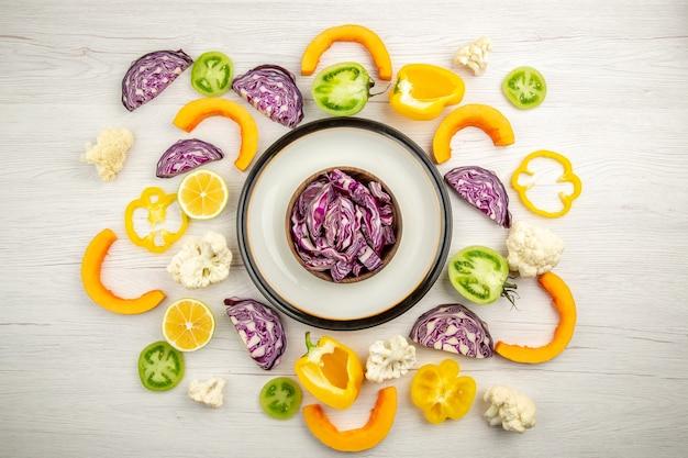 Vue de dessus couper les choux rouges dans un bol sur un plateau rond de légumes hachés sur une surface blanche