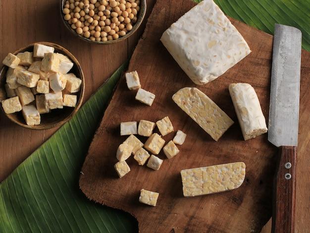 Vue de dessus couper le tempeh cru en tranches sur une planche à découper en bois au-dessus d'une table marron rustique avec une feuille de bananier
