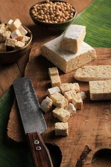 Vue de dessus couper le tempeh cru en tranches sur une planche à découper en bois au-dessus d'une table marron rustique