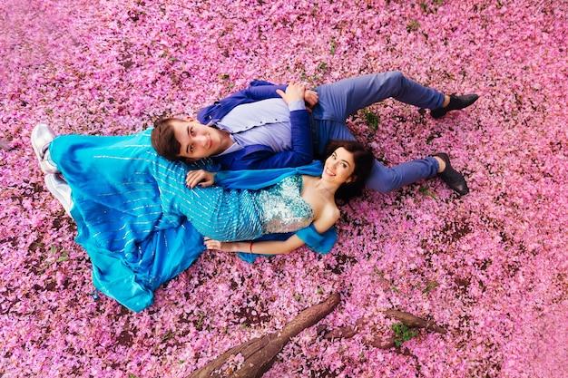 Vue de dessus d'un couple amoureux qui se trouvent sur le sol parmi les pétales de fleurs