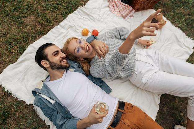 Vue de dessus couple ayant un pique-nique ensemble à l'extérieur