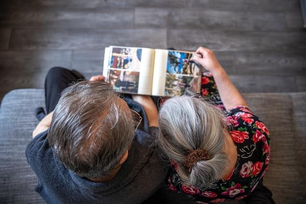 Vue de dessus un couple de personnes âgées regarde un album photo de famille.