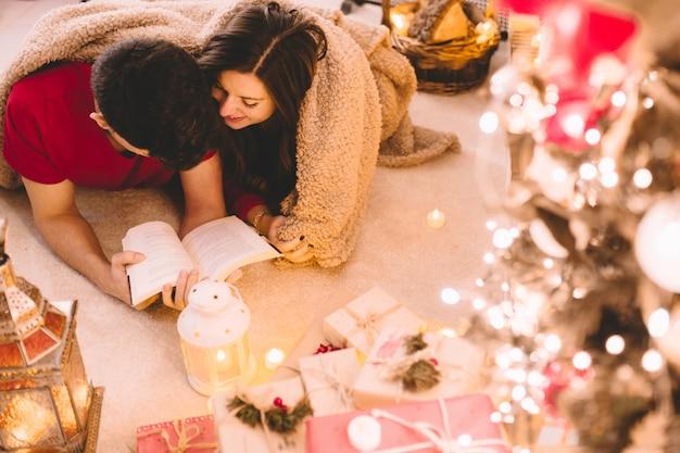 Vue de dessus d'un couple relaxant couvert par une couverture douce et confortable à la maison en lisant un livre ensemble sous la cheminée avec des bougies, des cadeaux et un arbre décoré.