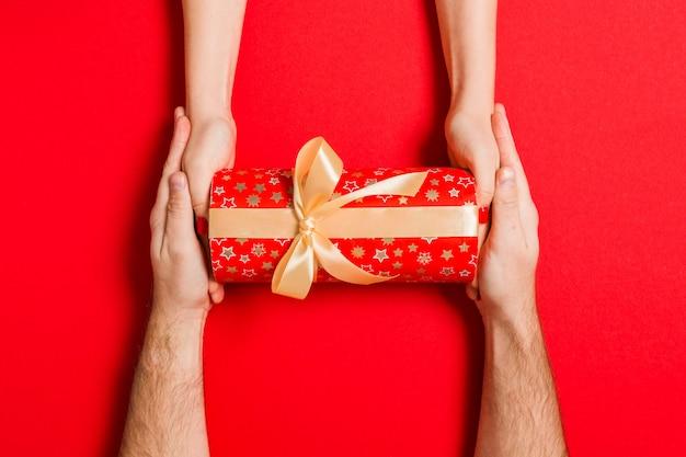 Vue de dessus d'un couple se félicitant mutuellement pour un fond coloré. donner un cadeau.