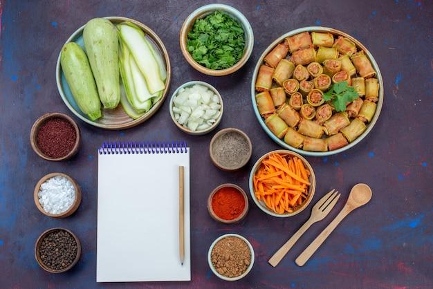 Vue de dessus des courges fraîches avec des verts et des assaisonnements rouleaux de viande et bloc-notes sur le repas de légumes de dîner de viande de bureau violet foncé