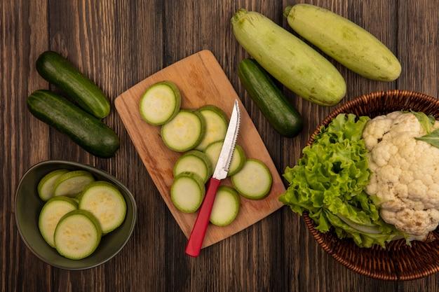 Vue de dessus des courgettes hachées sur un bol avec des courgettes hachées sur une planche de cuisine en bois avec un couteau avec du chou-fleur et de la laitue sur un seau avec du concombre et des courgettes isolé sur un mur en bois