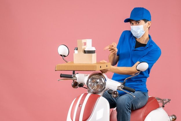 Vue de dessus d'un coursier travailleur en masque médical portant un chapeau assis sur un scooter sur fond de pêche pastel