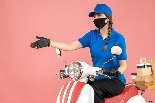 Vue de dessus d'une coursière curieuse portant un masque médical et des gants assis sur un scooter livrant des commandes sur fond de pêche pastel