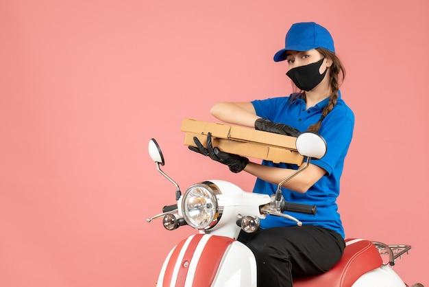 Vue de dessus d'une coursière occupée portant un masque médical et des gants assis sur un scooter livrant des commandes sur fond de pêche pastel