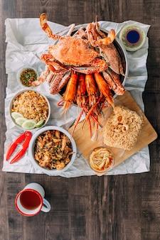 Vue de dessus des crabes de boue géants cuits à la vapeur, des crevettes grillées (crevettes), du riz frit au crabe, du crabe à carapace molle au poivre et à l'ail, du poisson-chat croustillant, de la salade de mangue et de la sauce de fruits de mer épicée thaïlandaise. servi avec de la bière.