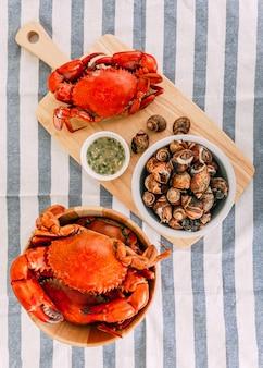 Vue de dessus de crabes géants cuits à la vapeur dans un bol en bois servis avec une sauce thaïlandaise aux fruits de mer épicée