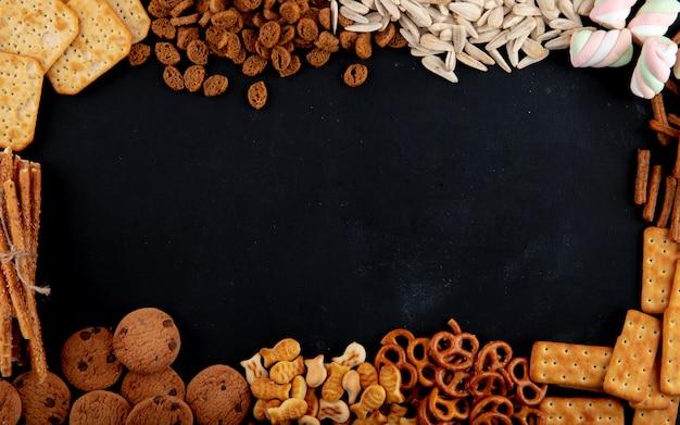 Vue de dessus des crackers avec des biscuits biscuits et des graines sur un fond noir