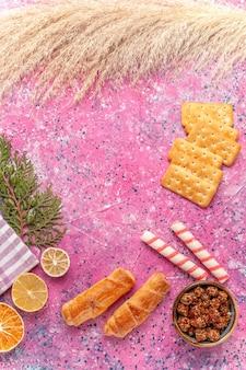 Vue de dessus des craquelins et des bagels sur la couleur de collation croquante rose sucré