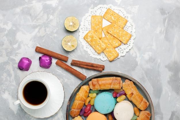 Vue de dessus des craquelins et des bagels avec une tasse de thé sur blanc