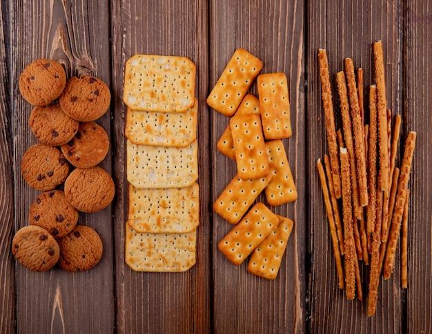 Vue de dessus des craquelins avec des biscuits et des gressins sur une table en bois