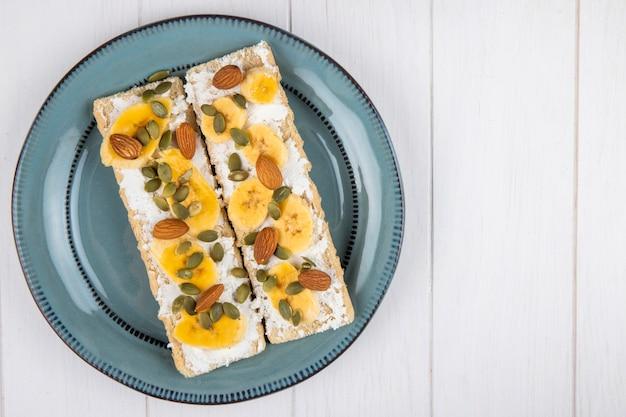 Vue de dessus des craquelins croustillants au fromage à la crème, des tranches de banane, d'amande et de graines de citrouille sur une plaque en bois blanc avec copie espace