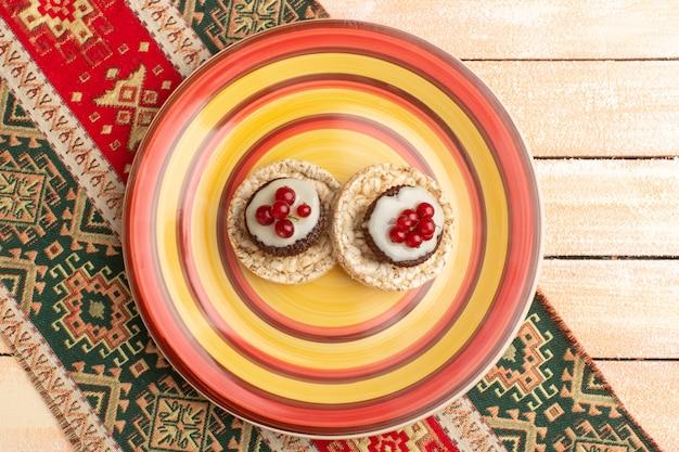 Vue de dessus des craquelins et des gâteaux aux canneberges sur le dessus à l'intérieur de la plaque colorée