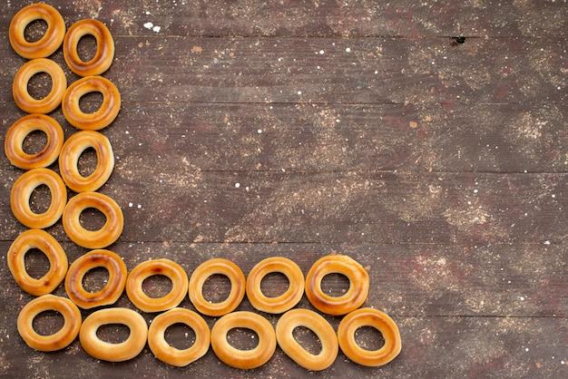Vue de dessus des craquelins ronds sucrés séchés et des collations savoureuses alignées sur brun, biscuit biscuit petit déjeuner