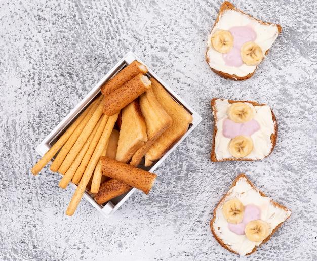 Vue de dessus des craquelins et des toasts sur une surface blanche horizontale