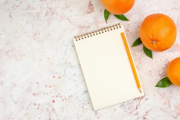 Vue de dessus crayon orange oranges fraîches sur le bloc-notes sur une surface isolée lumineuse avec un espace libre